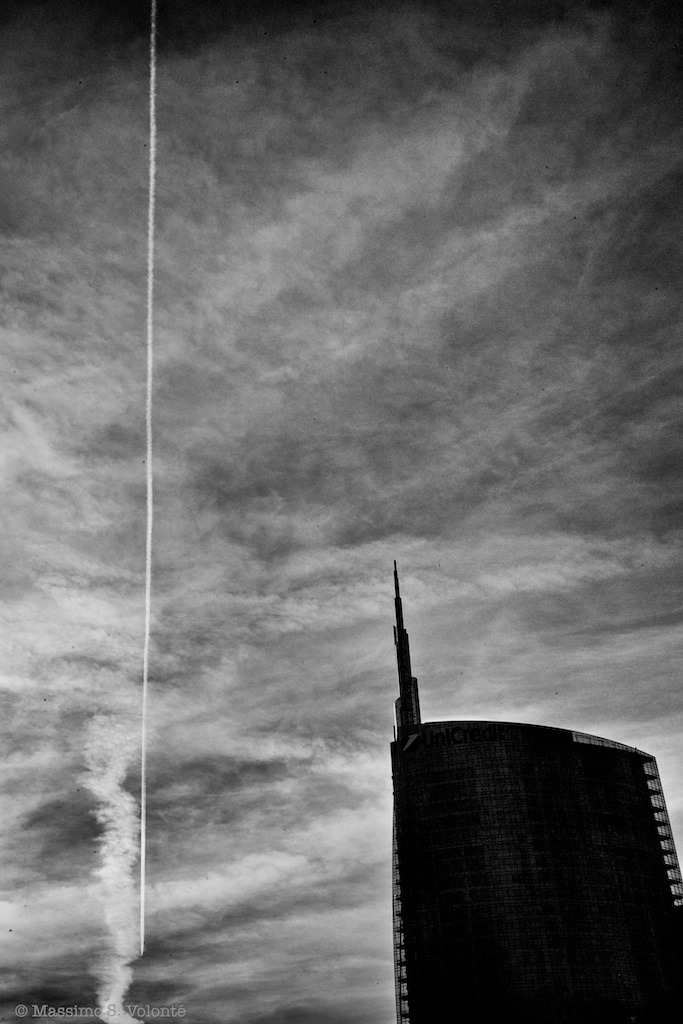 skyscraper silhouette and airplane striation