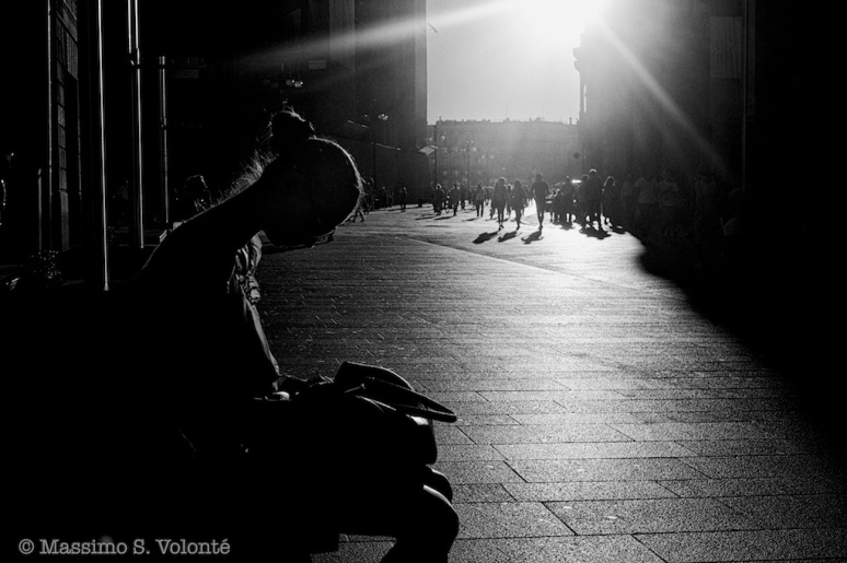 Waiting for the sun - A girl seating on a bench in the city center with sun going down