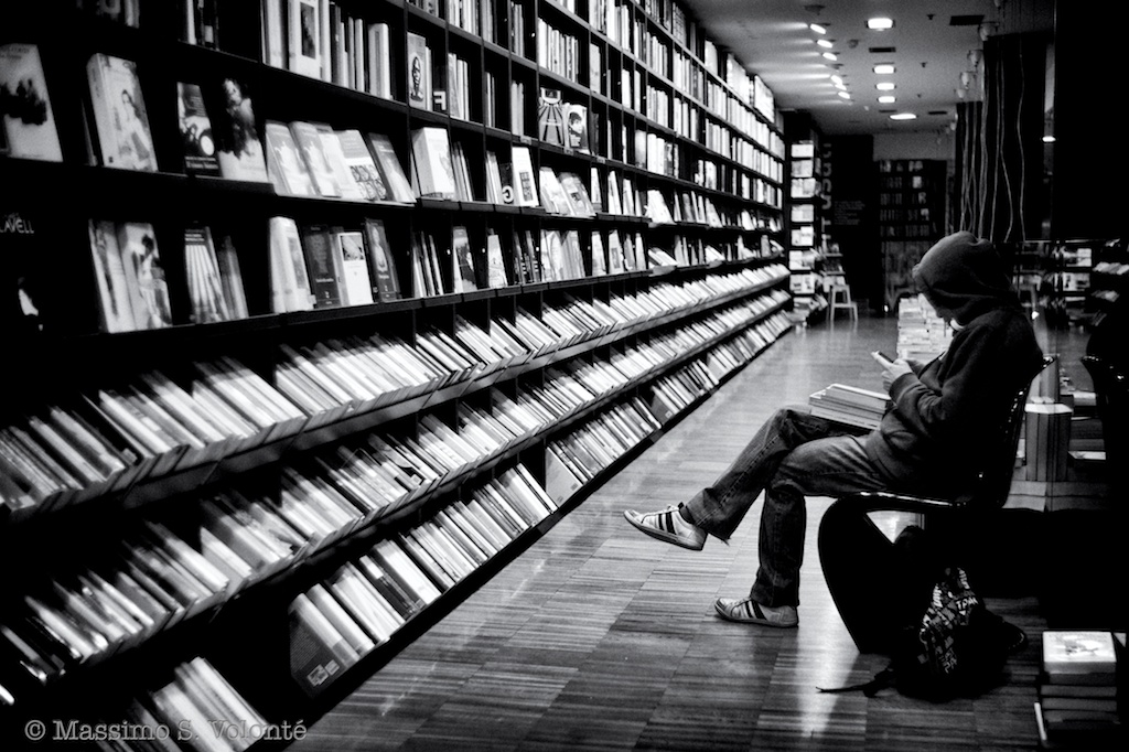 Symptom of the universe 1 - A person seated in front of a long bookshelf in a store