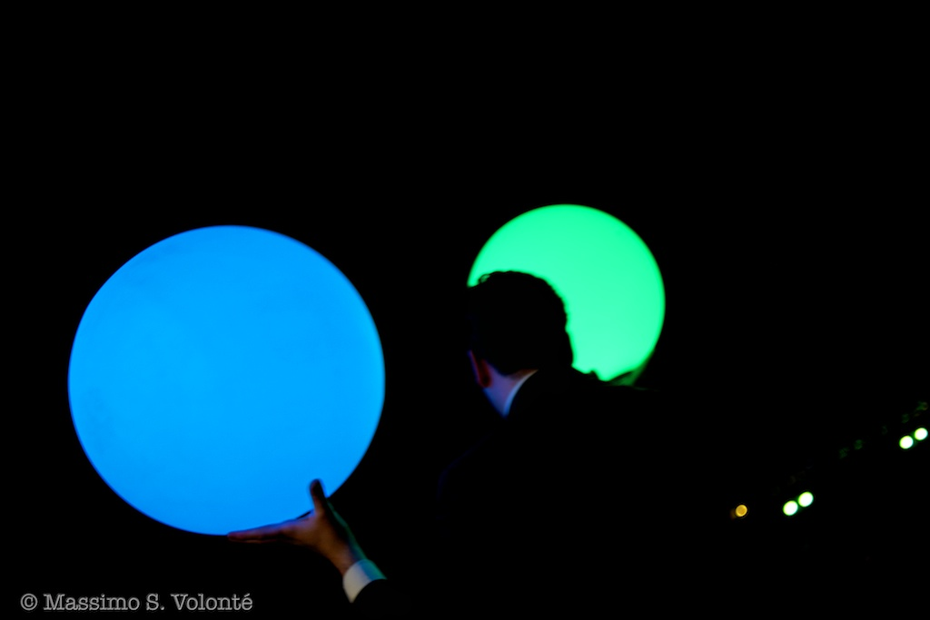 SU0019 - A man is carring two big colored enlightened balls