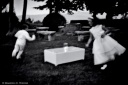 Young boy and girl playing chasing each other around a table
