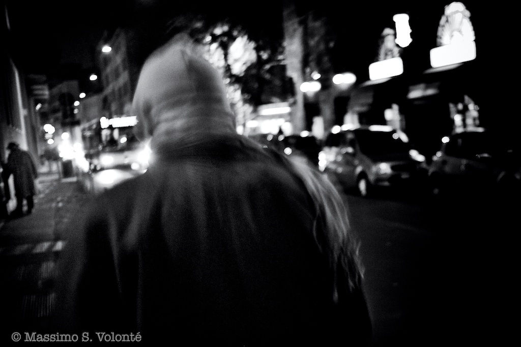 Man walking down a city street at night seen from behind
