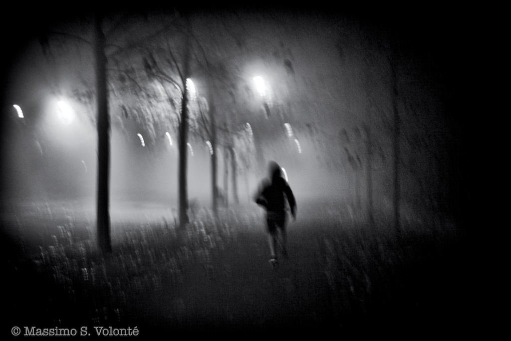 Lonely person walking in the mist of the park at night