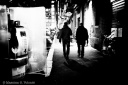 Two men walk away from a telephone booth in the city of nothing at night