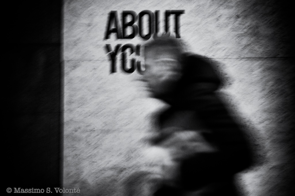 "Man passing and blurred by a ""About you"" graffiti"