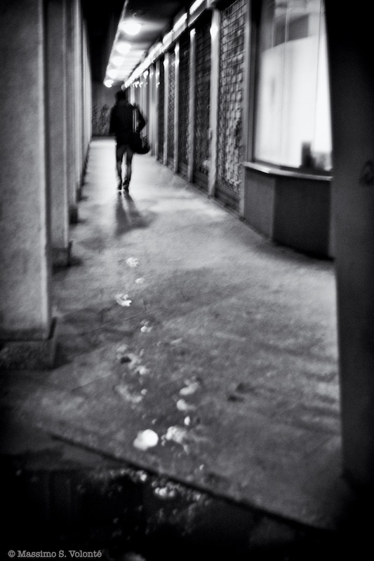 A lonely man walk away leaving behind him his wet footprints, monochrome, fotografo milano