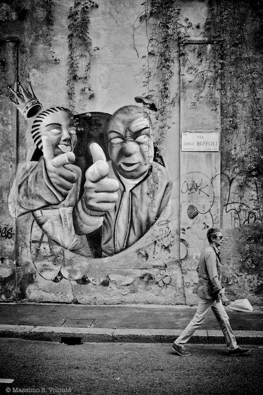 Man walking away from a graffiti on the city wall, fotografo milano