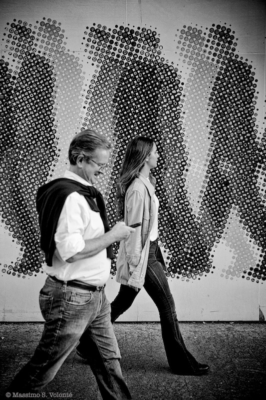 People passing by a billiborad of people passing by, monochrome, fotografo milano