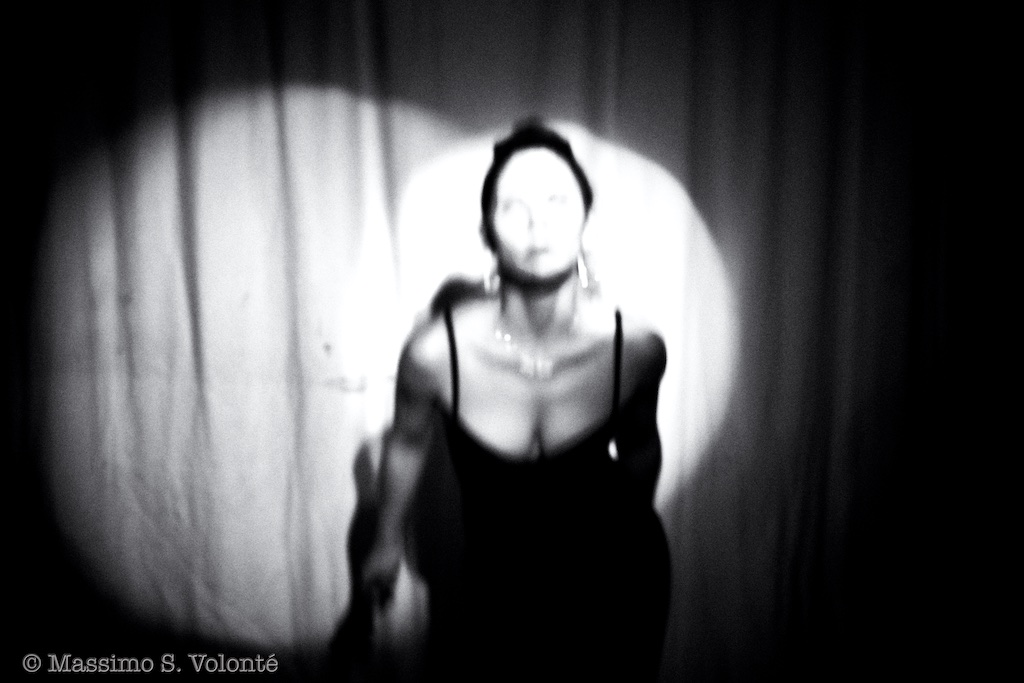 A woman without a face dancing in light beams, black and white, fotografo milano
