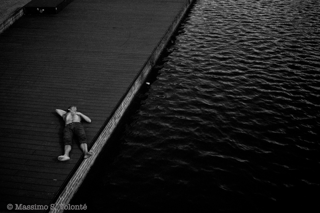A man lying down by a river bank, monochrome, fotografo MIlano