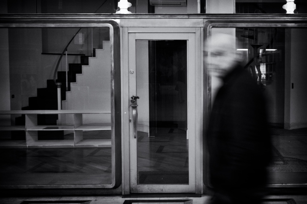 Man walking in front of emty store, Black and white, fotografo milano